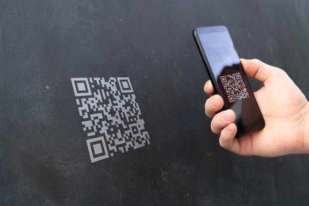 Une main tenant un smartphone et scannant le code qr pour effectuer un paiement