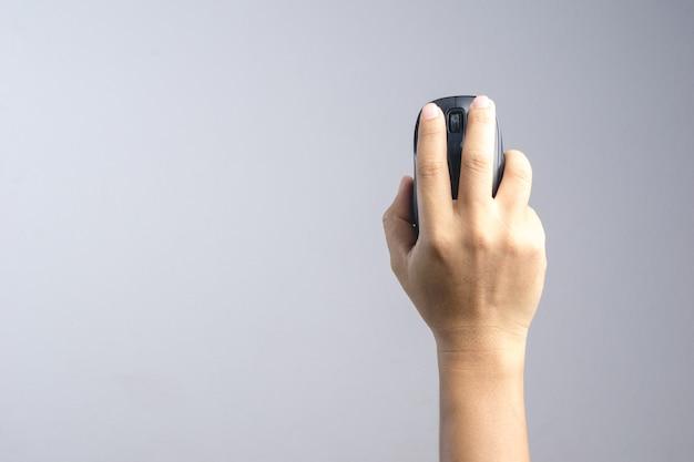 Main tenant une souris sans fil noire sur fond blanc