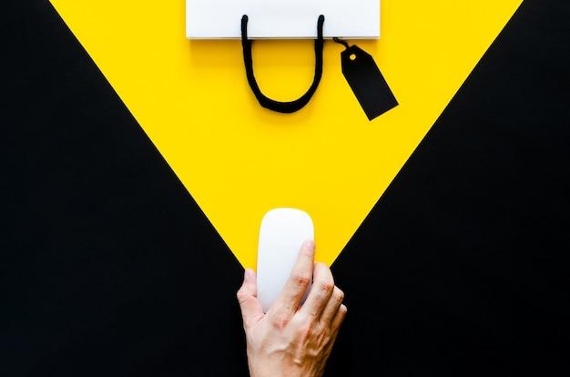 Main tenant une souris sans fil pour les achats en ligne avec un fond jaune et noir. concept de cyber monday et black friday.