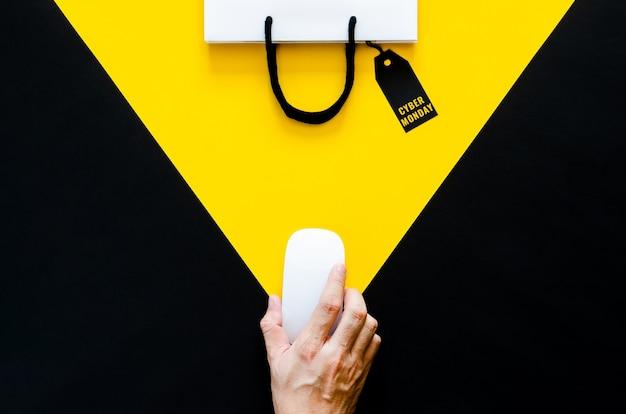 Main tenant une souris sans fil pour faire du shopping en ligne avec un fond jaune et noir. concept de cyber lundi.