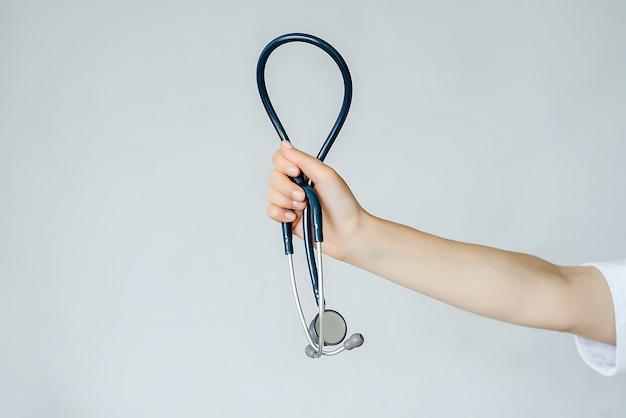 Main tenant le stéthoscope. le tout sur fond blanc.