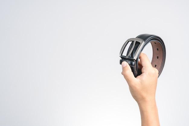 Main tenant le style ancien ou ceinture en cuir noir rétro avec tête en métal