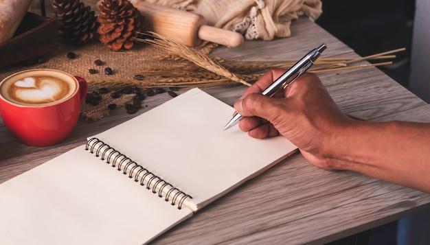 Main tenant un stylo écrit un cahier blanc étalé sur une table avec du café et du pain placés.