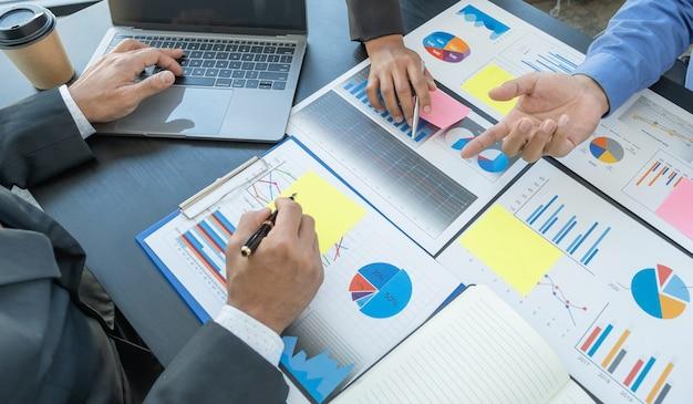 Main tenant un stylo, réunion de l'équipe de femmes d'affaires et d'hommes d'affaires pour planifier des stratégies visant à augmenter les revenus de l'entreprise