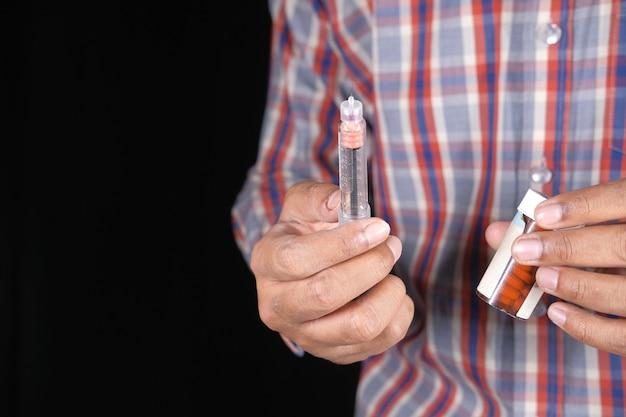 Main tenant des stylos à insuline et un contenant de pilules médicales sur fond noir