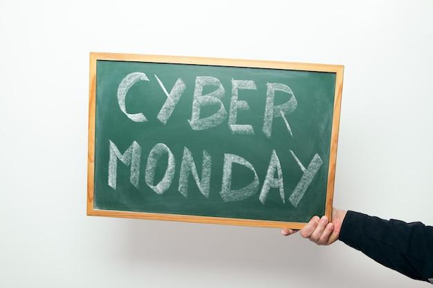 Main tenant un tableau avec les mots cyber monday manuscrits à la craie