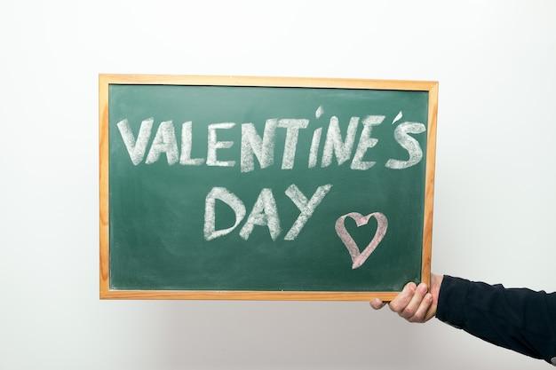 Main tenant un tableau avec les mots valentine's day manuscrits à la craie