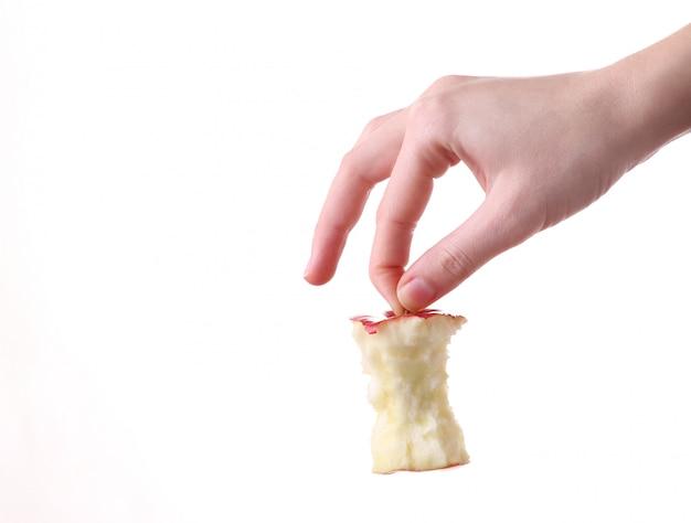 Main tenant le talon de pomme sur fond blanc