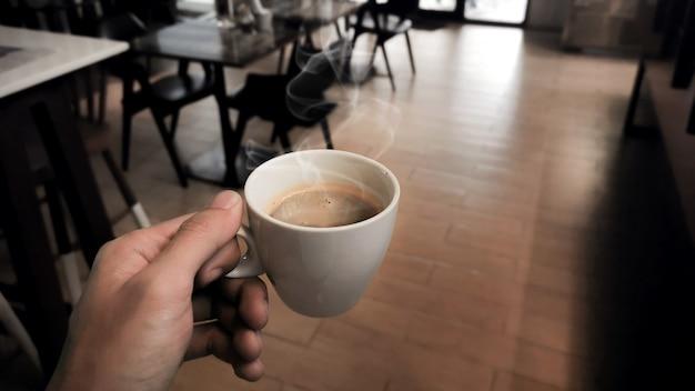 Main tenant une tasse blanche de café chaud