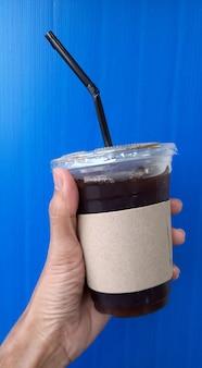 Main tenant une tasse de café, arrosage dans une tasse