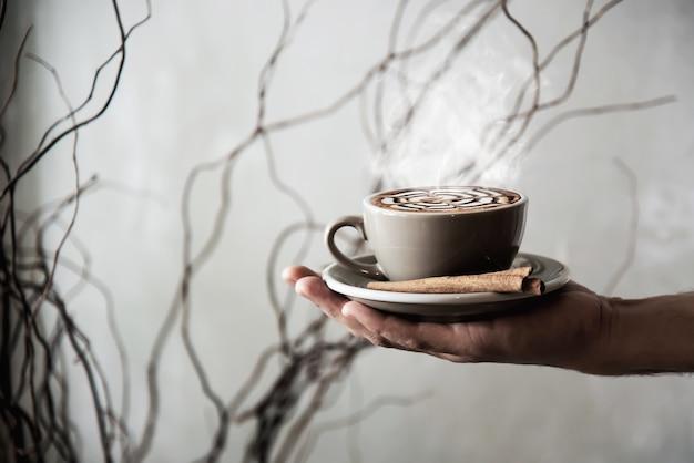 Main tenant une tasse de café chaud