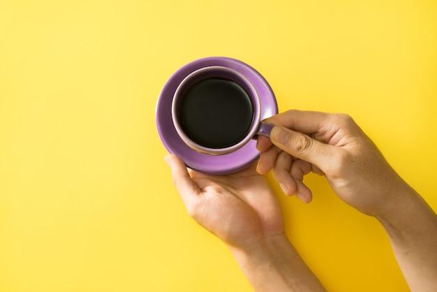 Main tenant une tasse de café sur le fond jaune