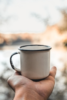 Main tenant une tasse de café sur fond naturel