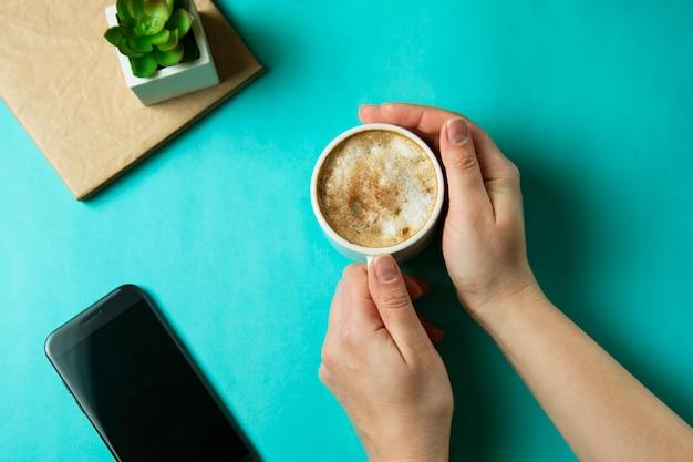 Main tenant la tasse à café avec des guimauves. plat poser, vue de dessus, bureau table bureau.
