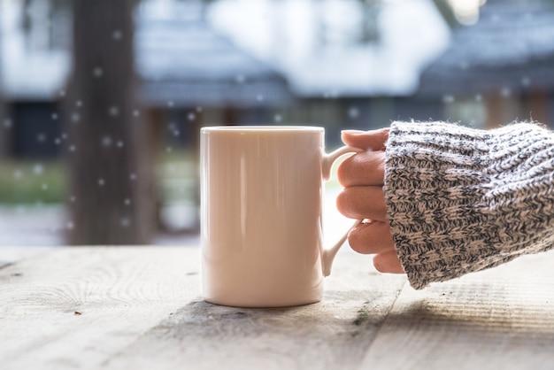 Main tenant une tasse de café le jour de l'hiver