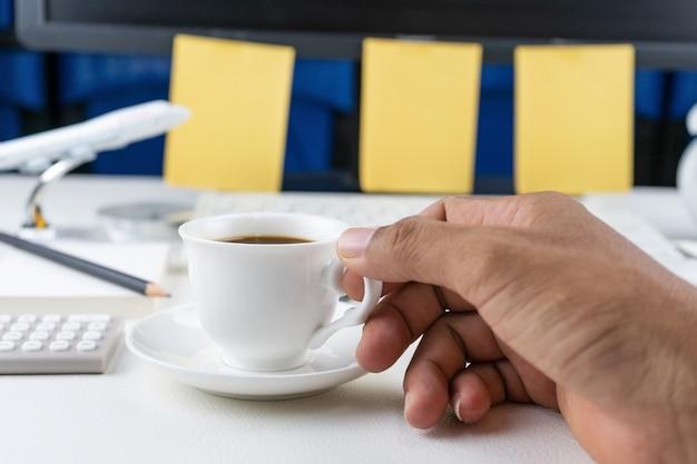 Main tenant la tasse de café avec des objets d'entreprise sur la table en cuir blanc.