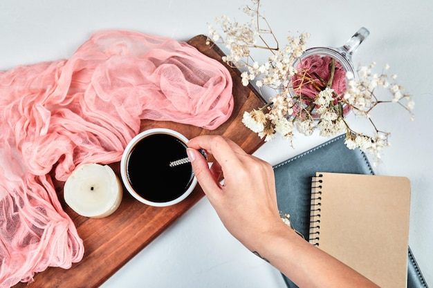Main tenant une tasse de café sur planche de bois avec bougie, tissu ponk et fleurs.