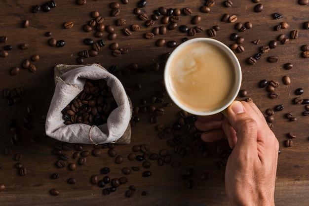 Main tenant une tasse de café près de sac avec des haricots