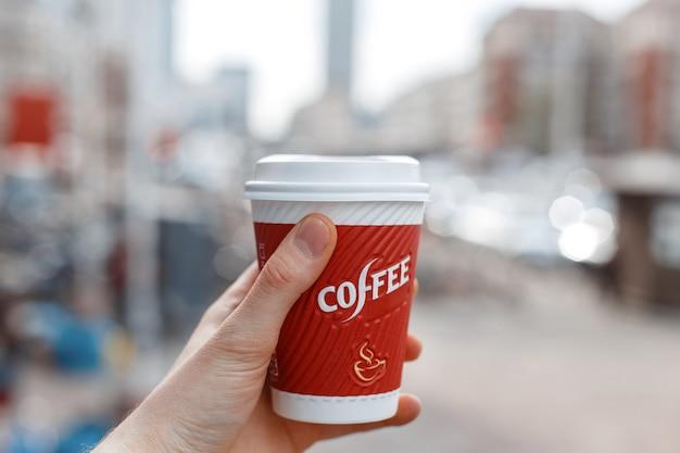 Main tenant une tasse de café rouge