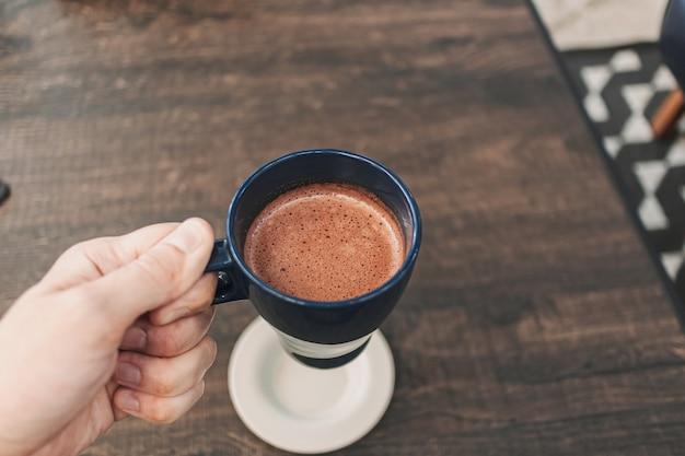 Main tenant une tasse de chocolat chaud dans un café