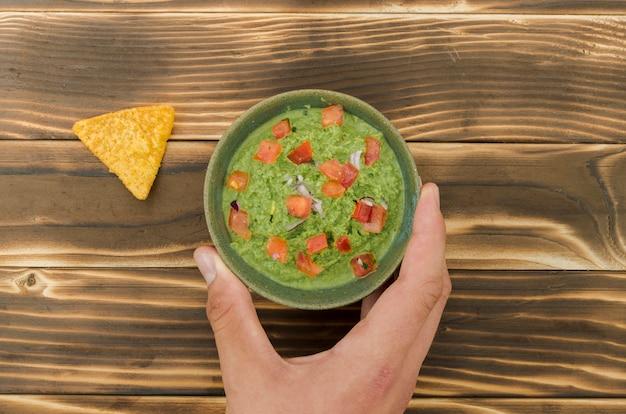 Main tenant une tasse de garniture près de nacho