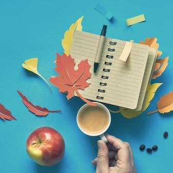 Main tenant la tasse d'offee, pomme et cahier avec des feuilles d'automne sur bleu