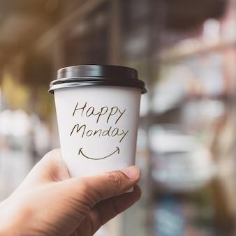 Main tenant une tasse de papier café blanc avec texte