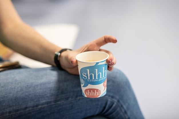 Main tenant une tasse, tasse à café en papier avec un café délicieux