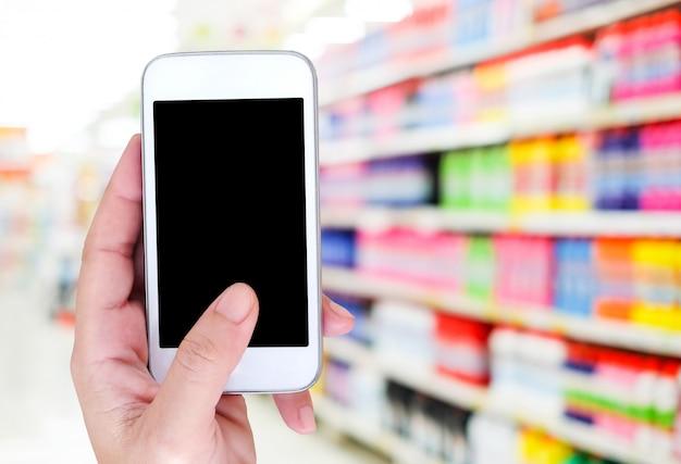 Main tenant un téléphone intelligent sur magasin flou