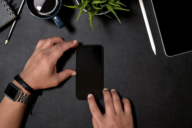 Main tenant un téléphone intelligent moderne avec écran blanc isolé pour maquette sur le bureau