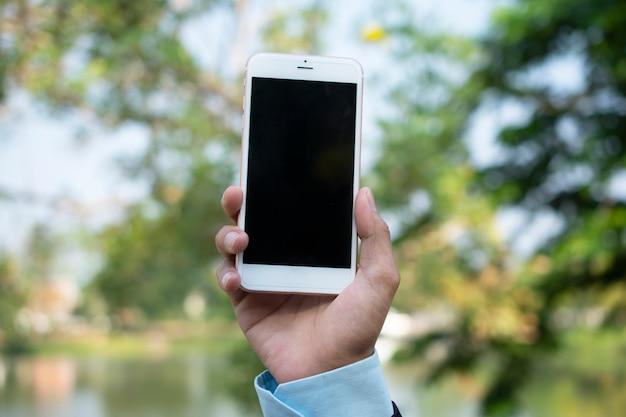 Main tenant un téléphone intelligent et utilisant un téléphone intelligent