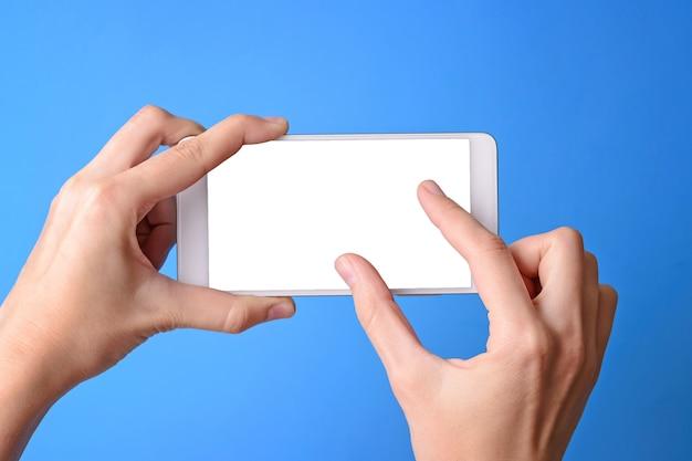 Main tenant le téléphone mobile et écran tactile isolé
