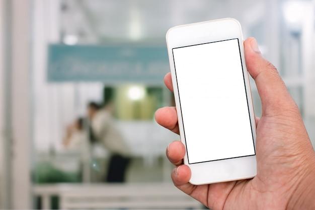 Main tenant un téléphone mobile intelligent avec un écran blanc en position verticale, arrière-plan flou - modèle de maquette