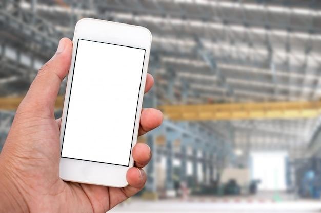 Main tenant un téléphone mobile intelligent avec écran blanc en position verticale