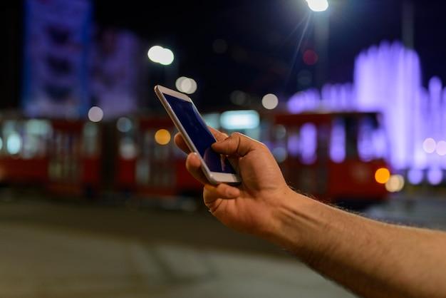 Main tenant un téléphone noir coupure à l'intérieur avec bokeh