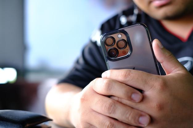 Main tenant un téléphone portable avec une caméra 3 voies