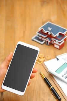 Main tenant un téléphone portable devant le modèle de maison