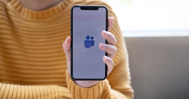 Une main tenant un téléphone portable avec une icône de deux personnes