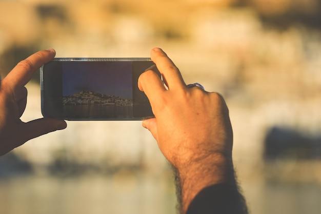 Main tenant un téléphone portable prenant une photo de la vieille ville d'ibiza