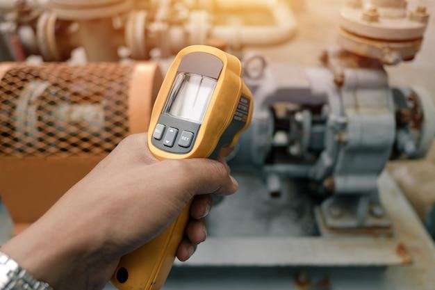 Main tenant un thermomètre infrarouge inspectant la machine