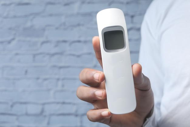 Main tenant un thermomètre infrarouge pour mesurer la température.