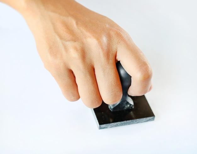 Main tenant le timbre en caoutchouc sur fond blanc