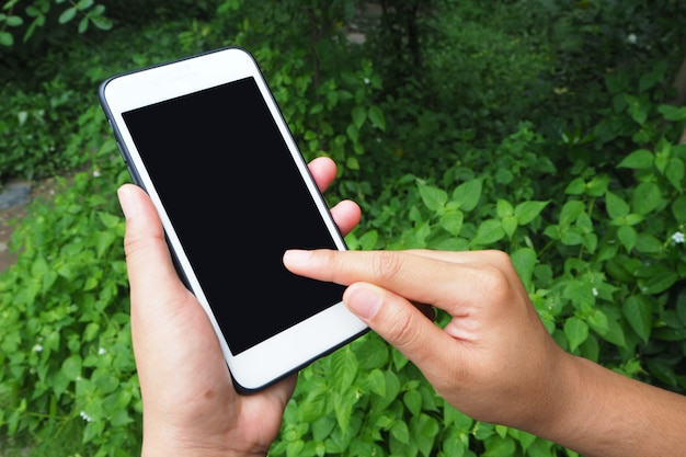 Main tenant et touchez sur smartphone avec un écran blanc sur fond de jardin.