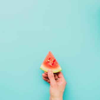 Main tenant une tranche de melon d'eau