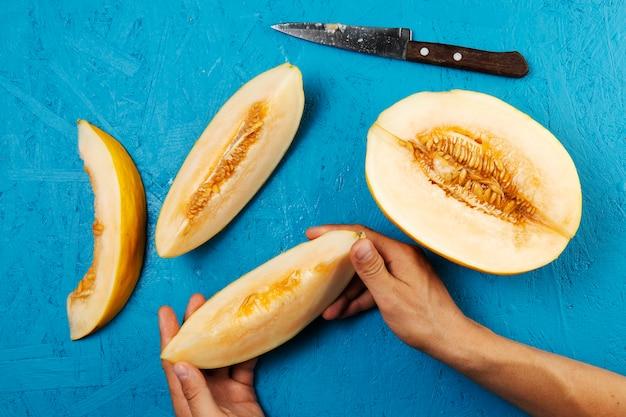 Main tenant une tranche de pastèque sur fond bleu