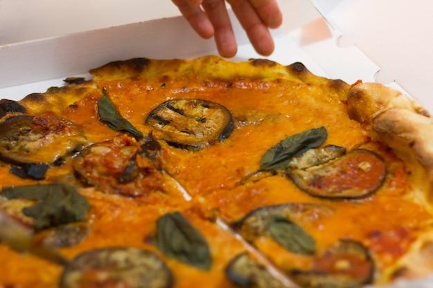 Main tenant une tranche de pizza végétarienne au basilic et aubergine