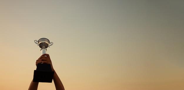 Main tenant un trophée sur le coucher du soleil