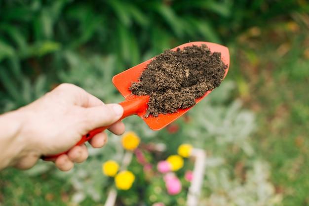 Main tenant une truelle avec terre