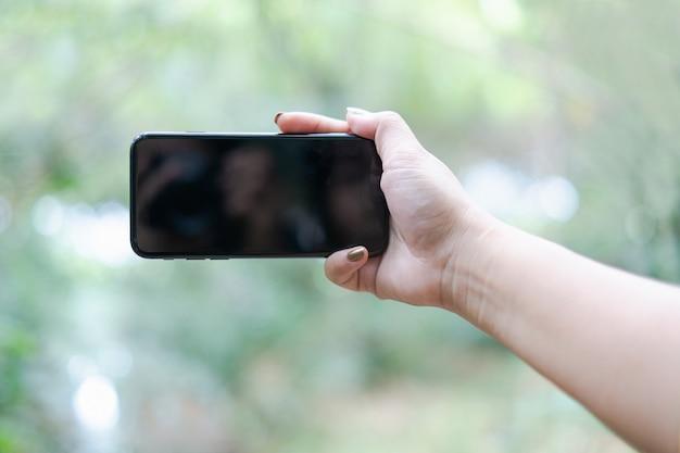 Main tenant et en utilisant un téléphone portable avec un écran blanc