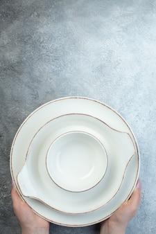 Main tenant de la vaisselle blanche sur le fond sur une surface gris clair à moitié foncé avec une surface en détresse